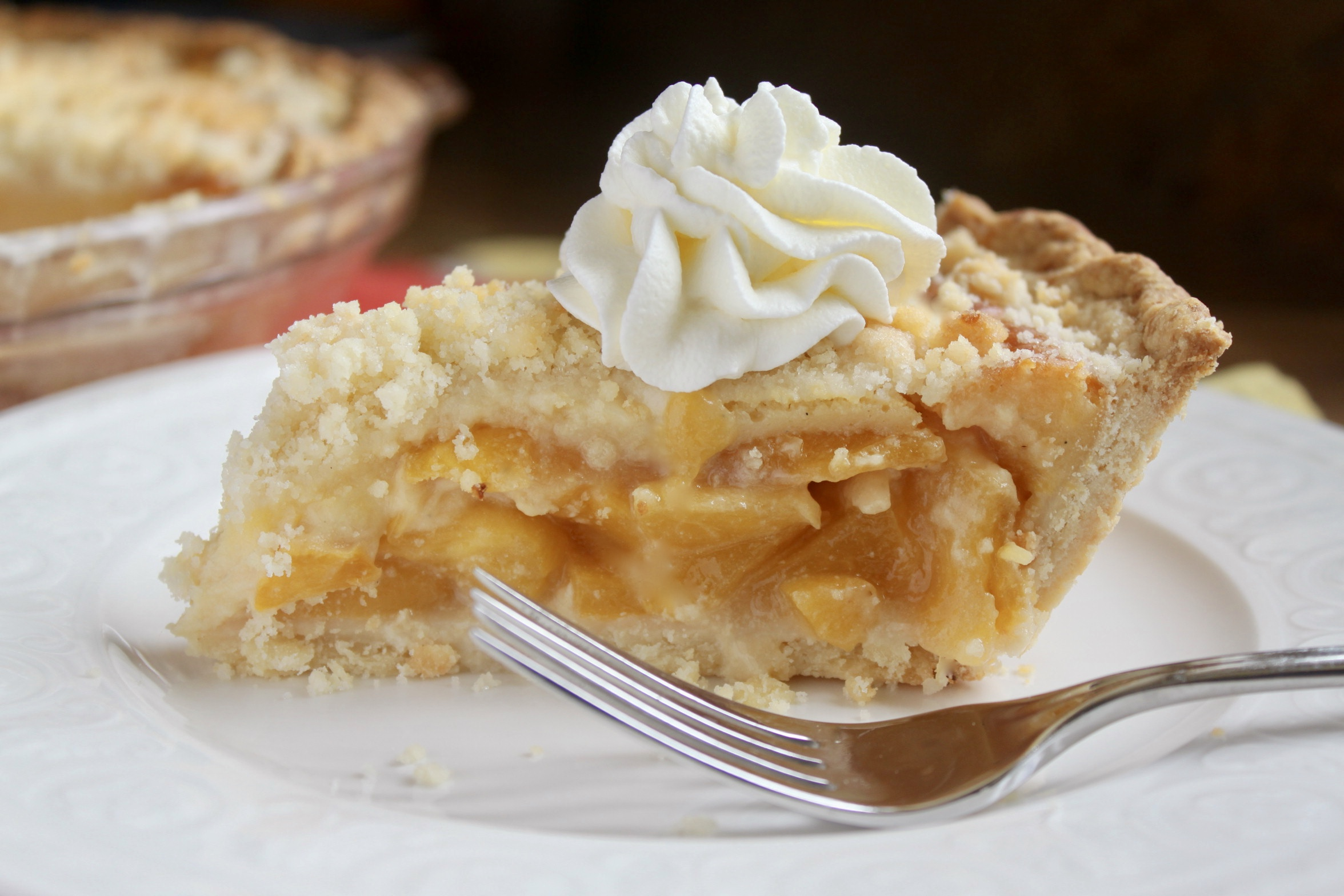 Slice of custard peach pie with cream