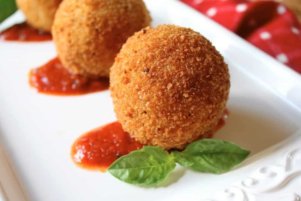 arancini on a plate with basil
