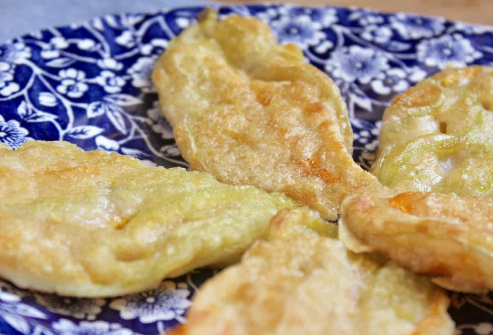 fried Italian zucchini blossoms on a floral plate