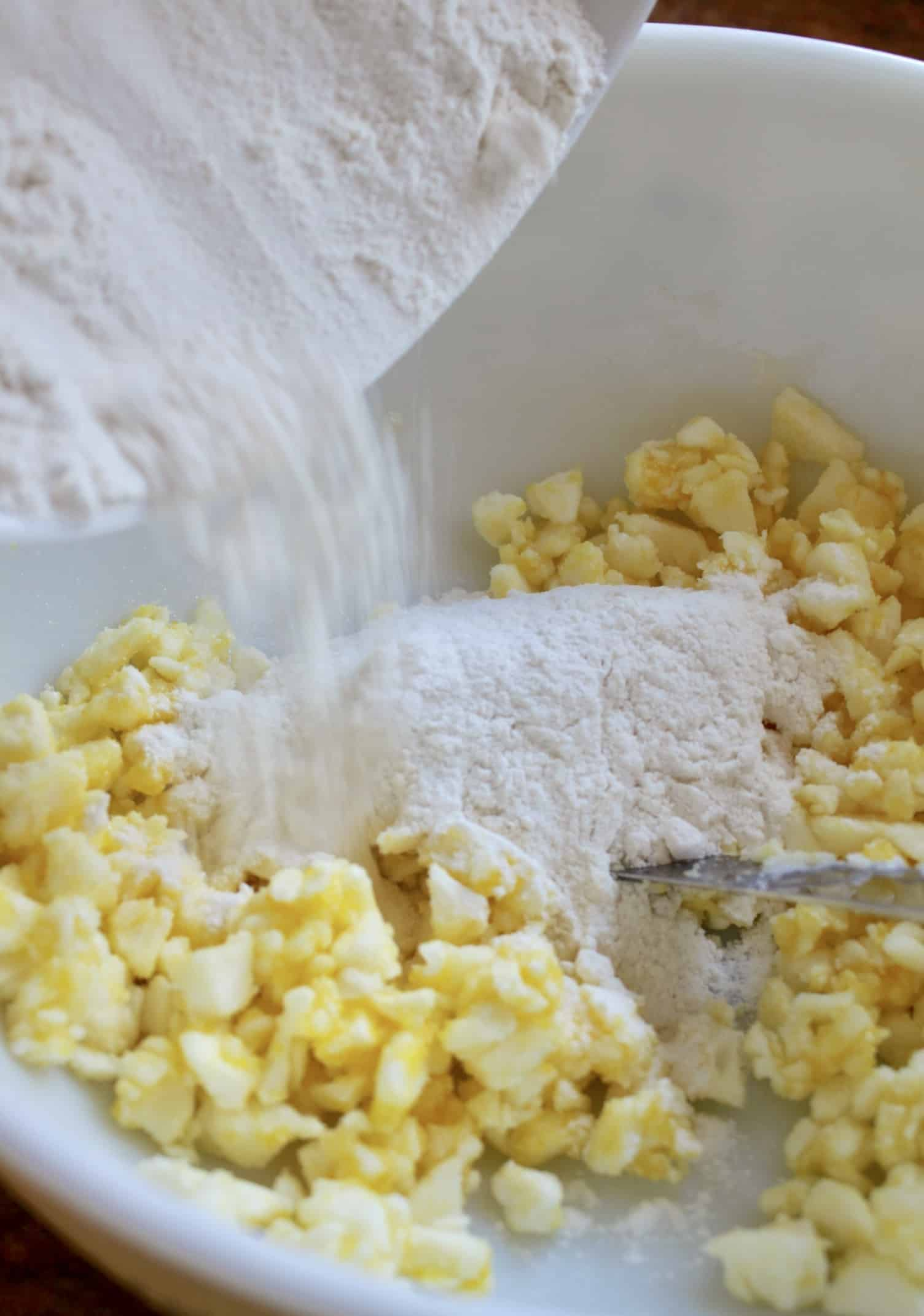adding flour to eggs, sugar and butter for Snow Cake