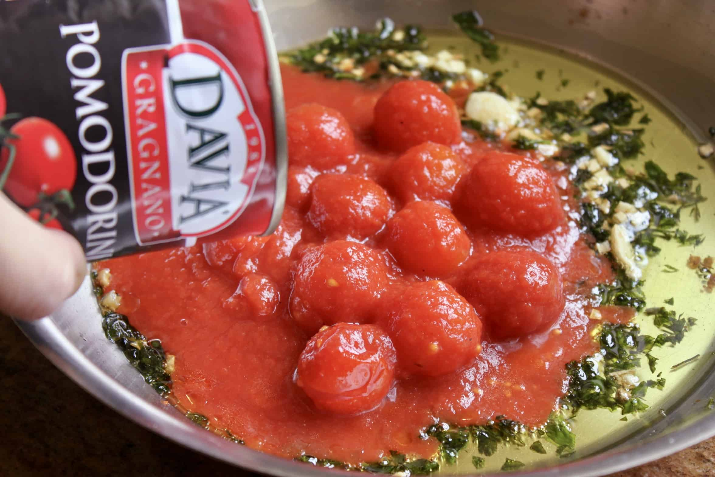 pouring davia tomatoes in a pan