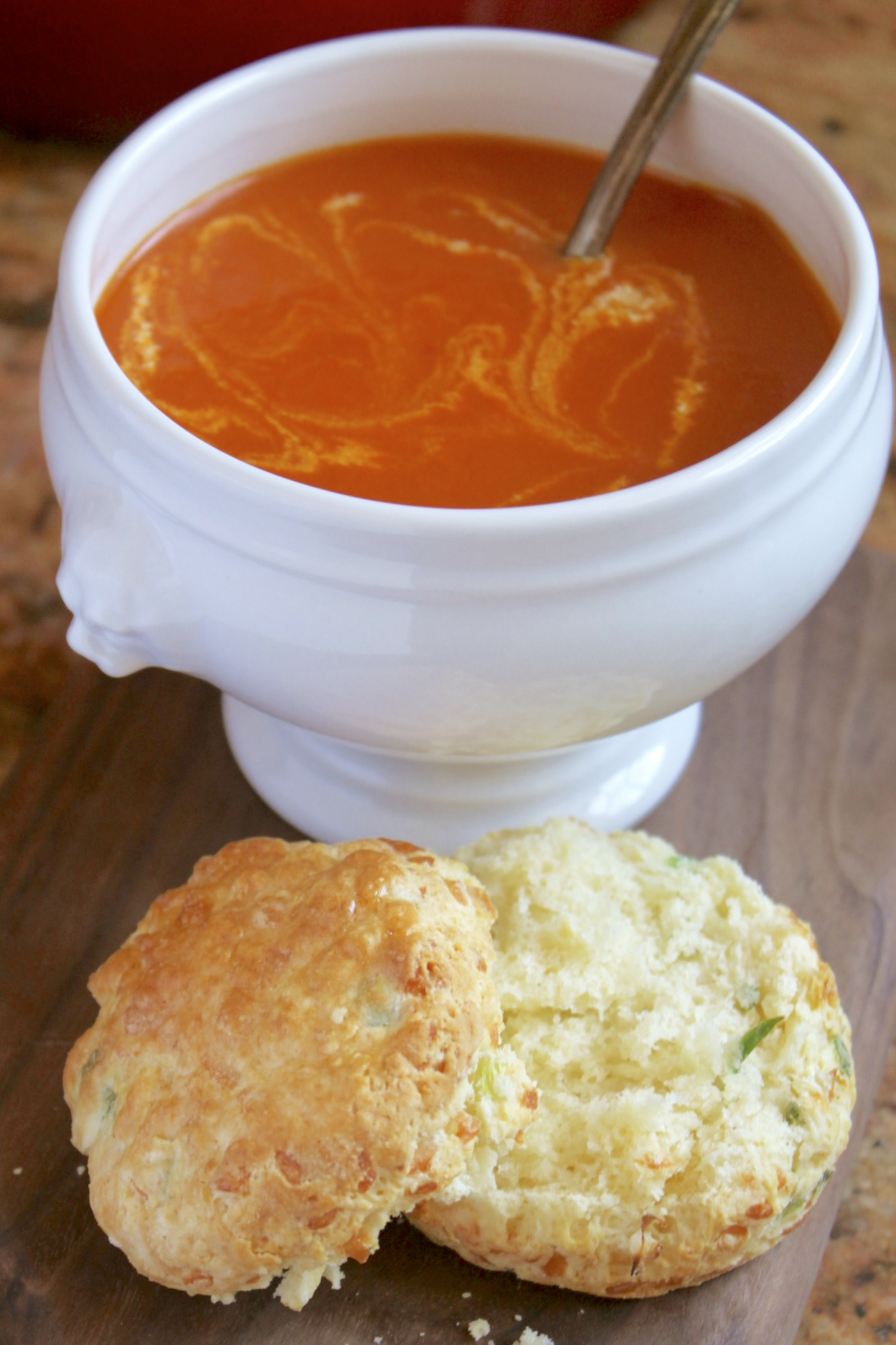 Tomato turmeric soup in a bowl with a cheese scone