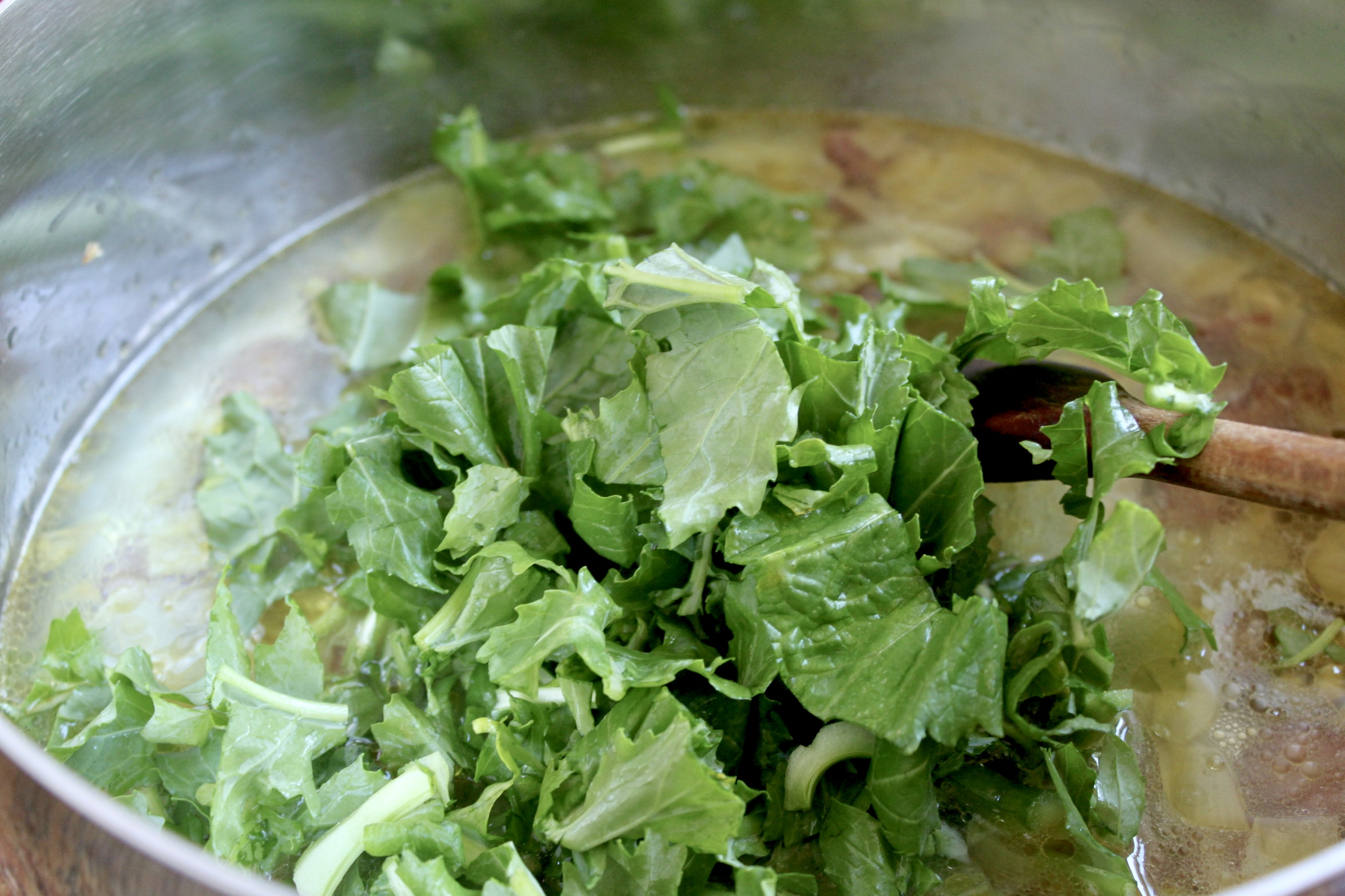 adding the rapini to the pot