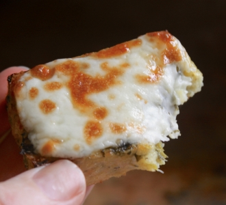 handheld piece of grilled polenta with cheese, bitten
