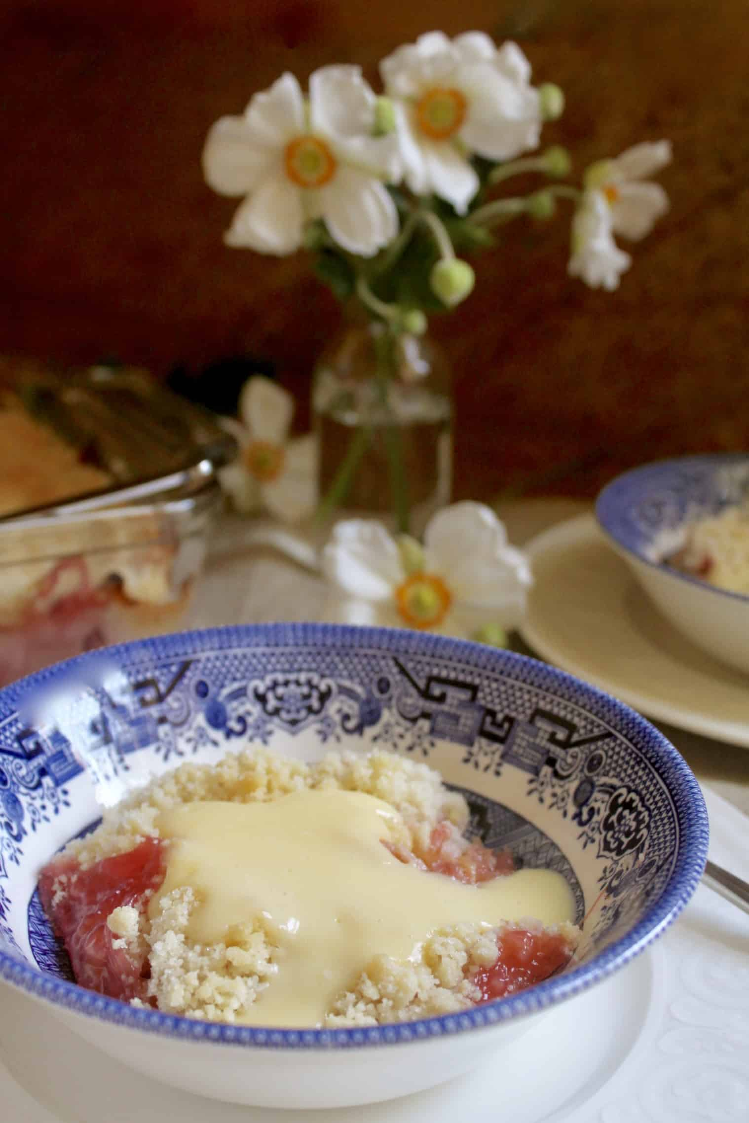 rhubarb crumble and custard in a bowl with flowers