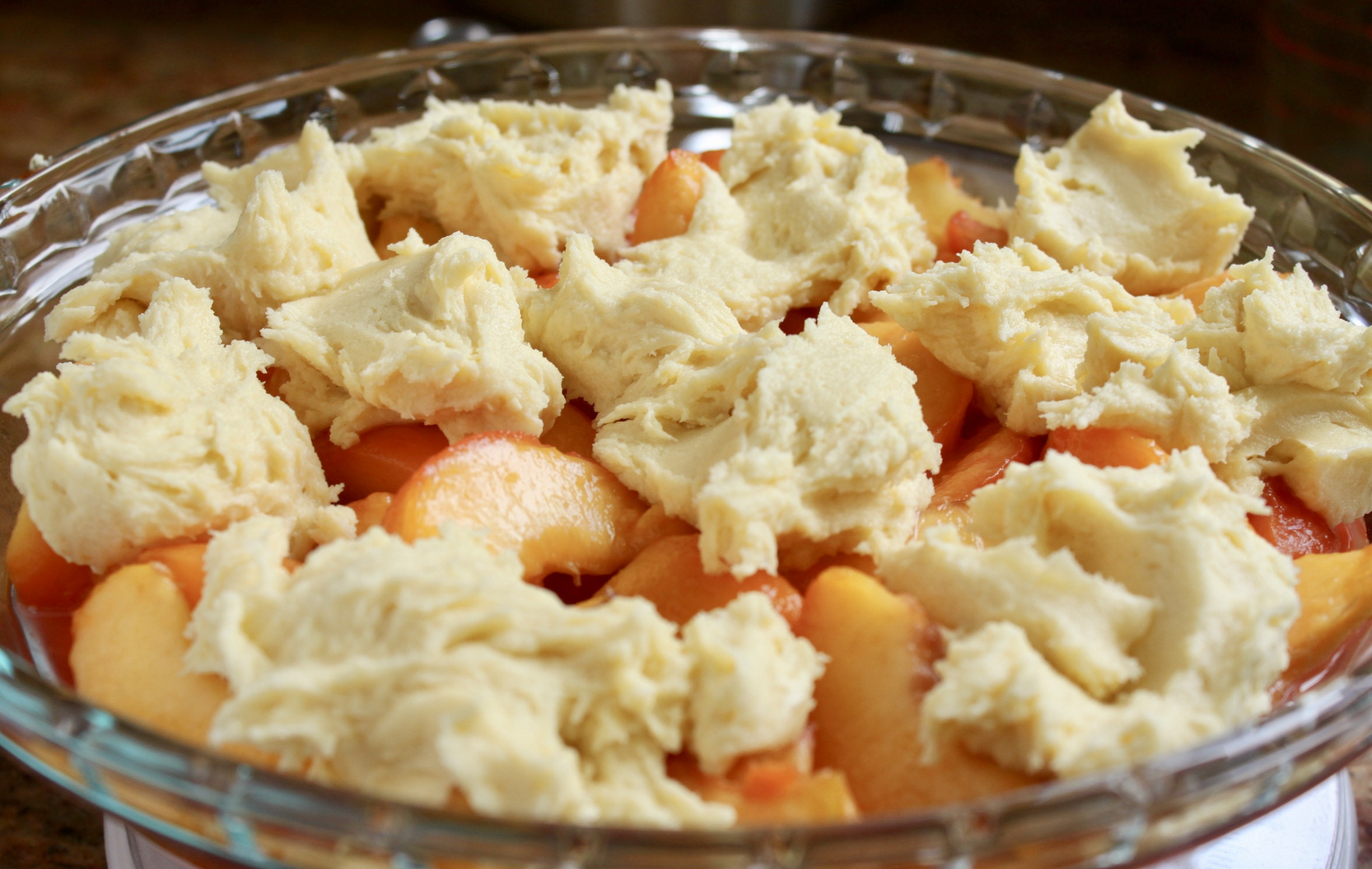 dough on top of peaches in pie dish