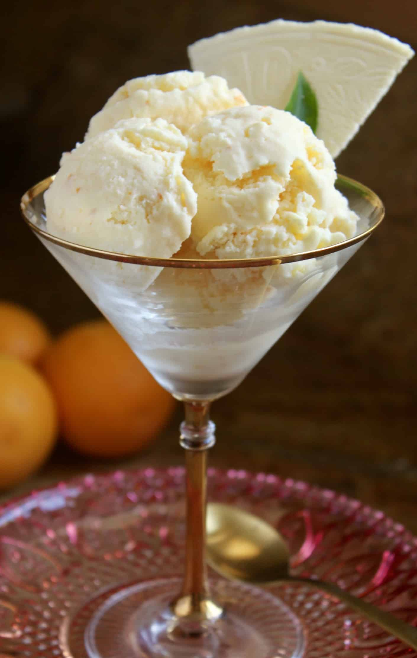 three scoops of orange ice cream and a wafer in a martini glass