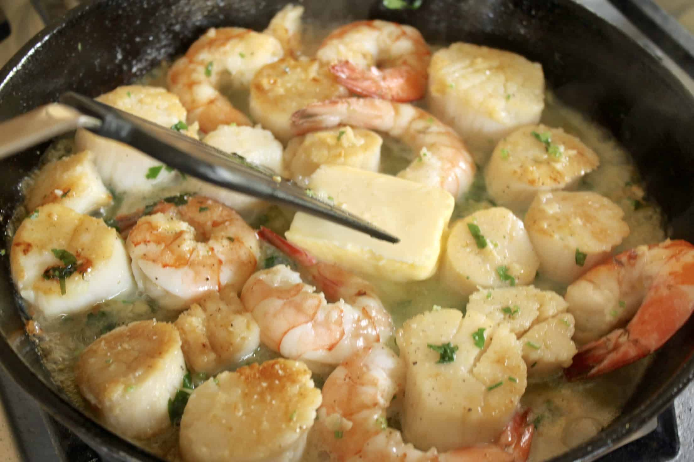 adding butter to seafood sauce