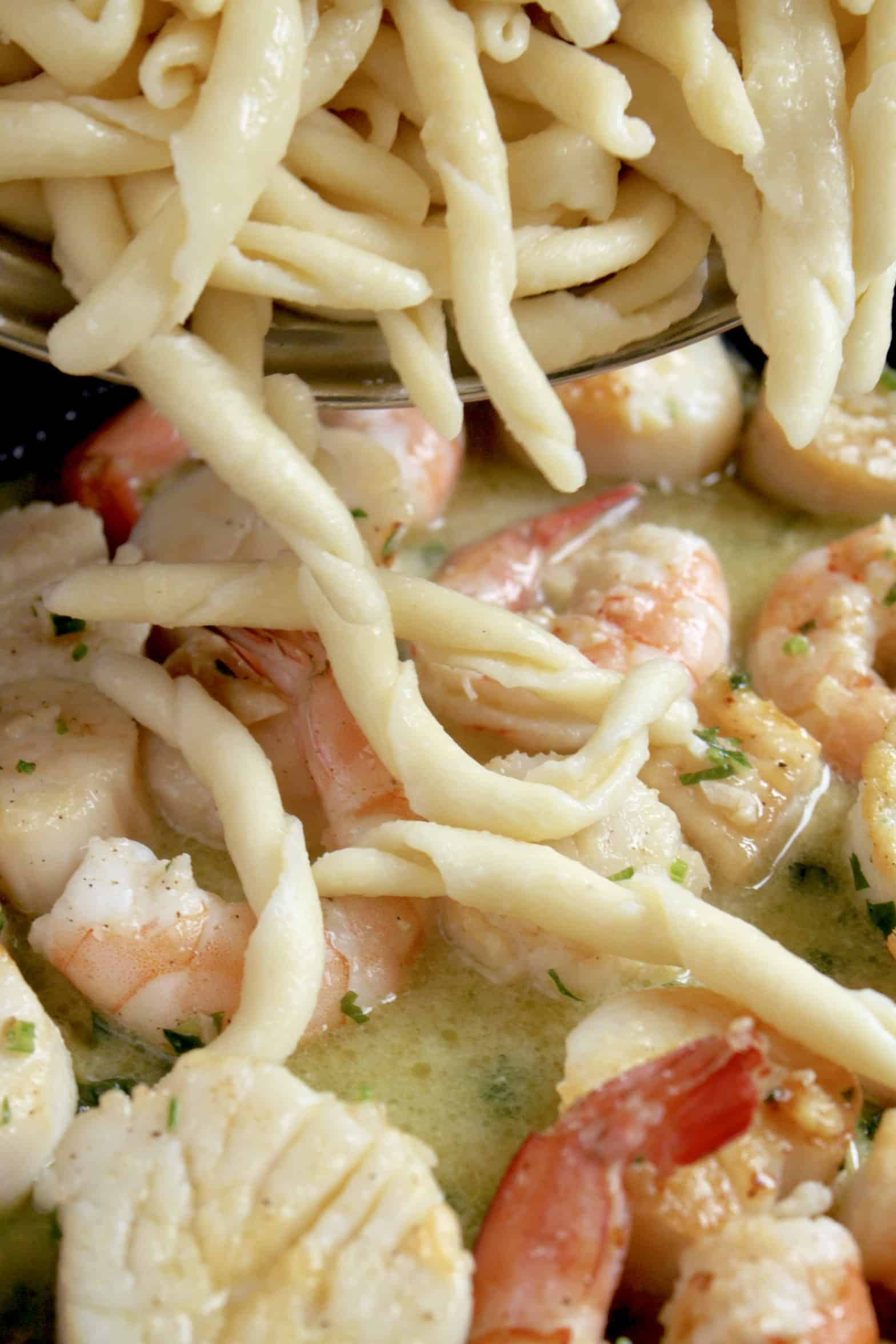 adding pasta to seafood in pan