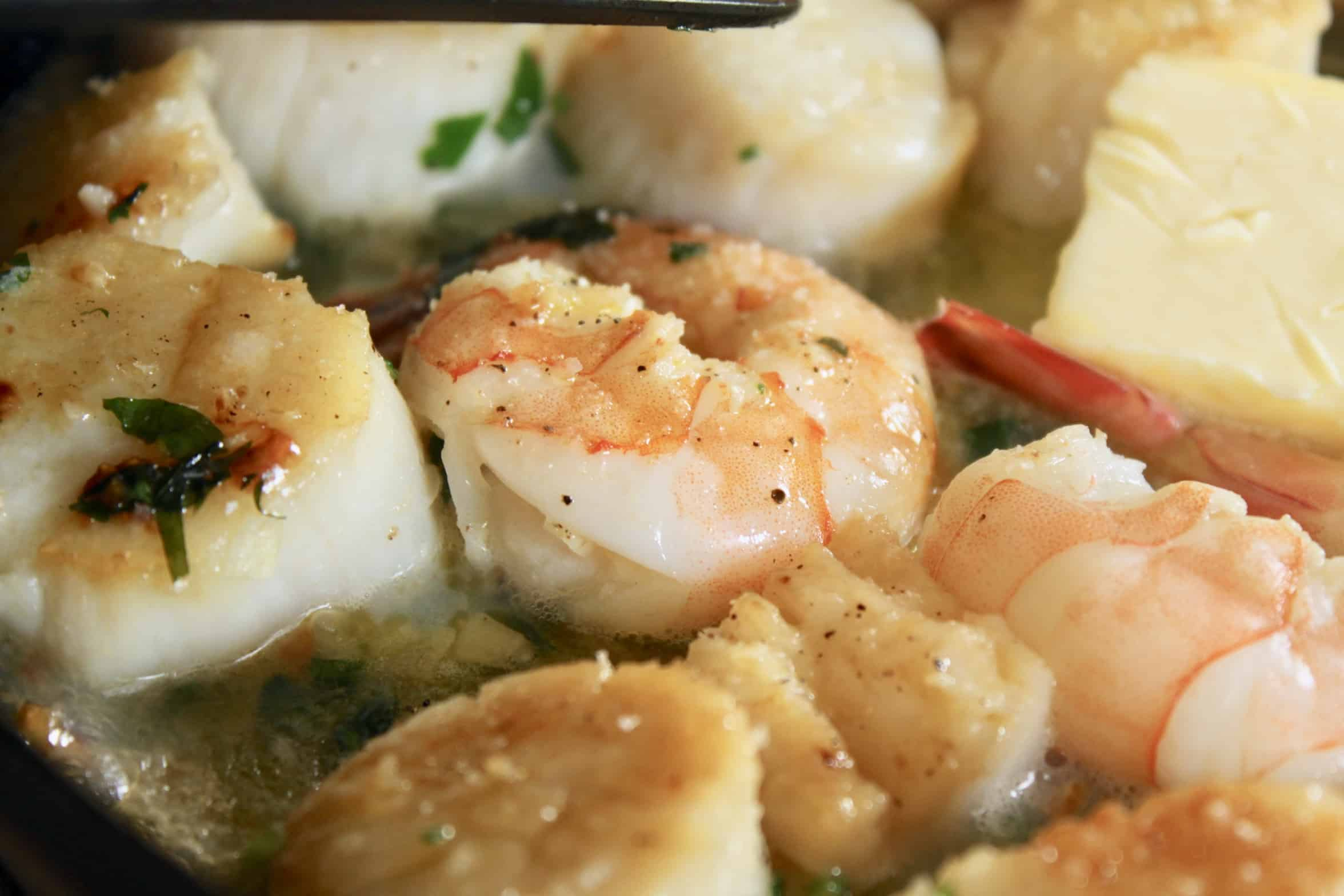 close up of shrimp and scallops in pan