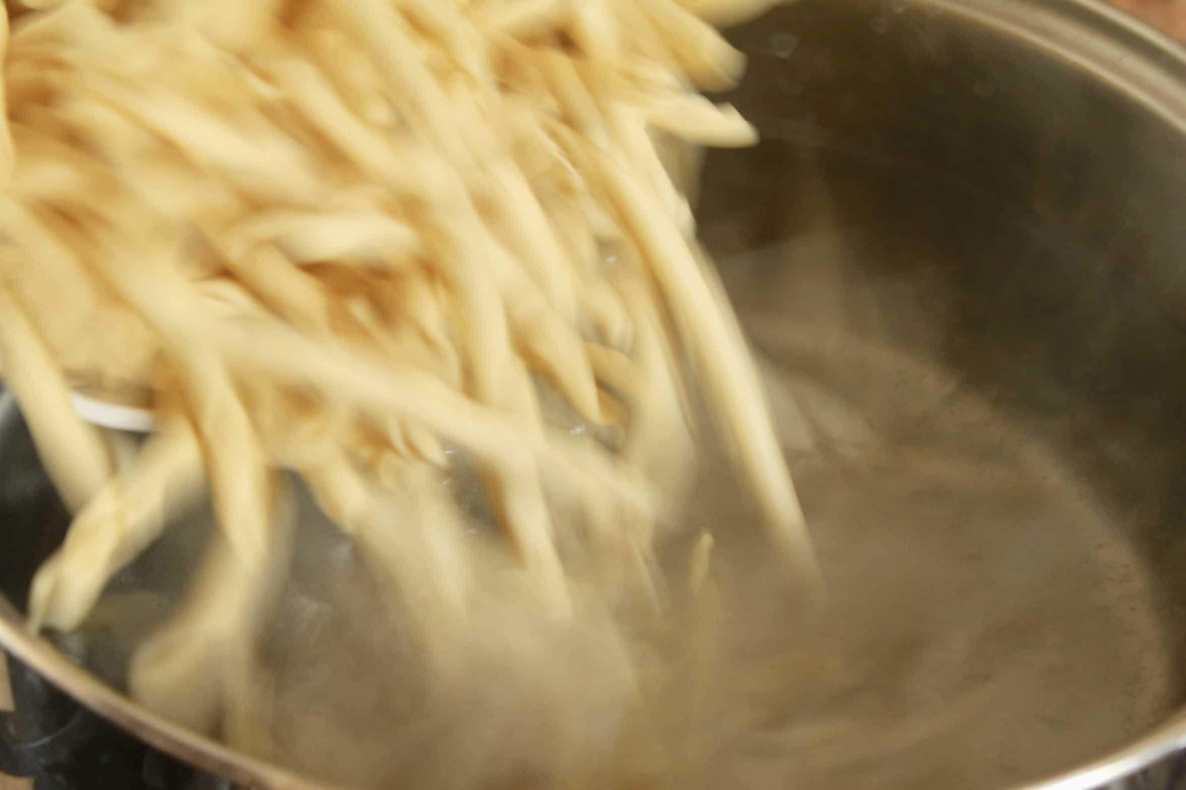 adding pasta to water
