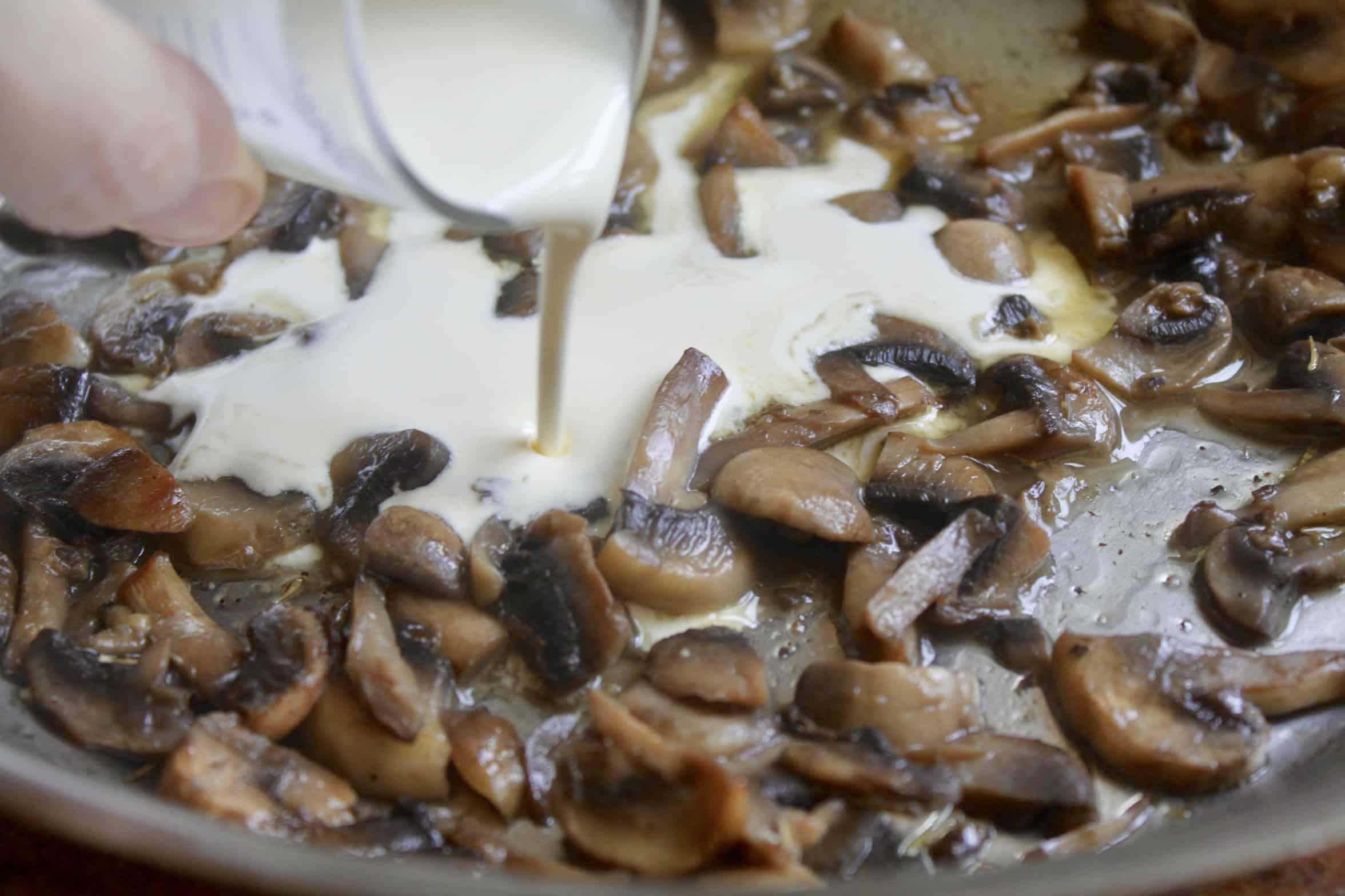 adding cream to mushroom sauce