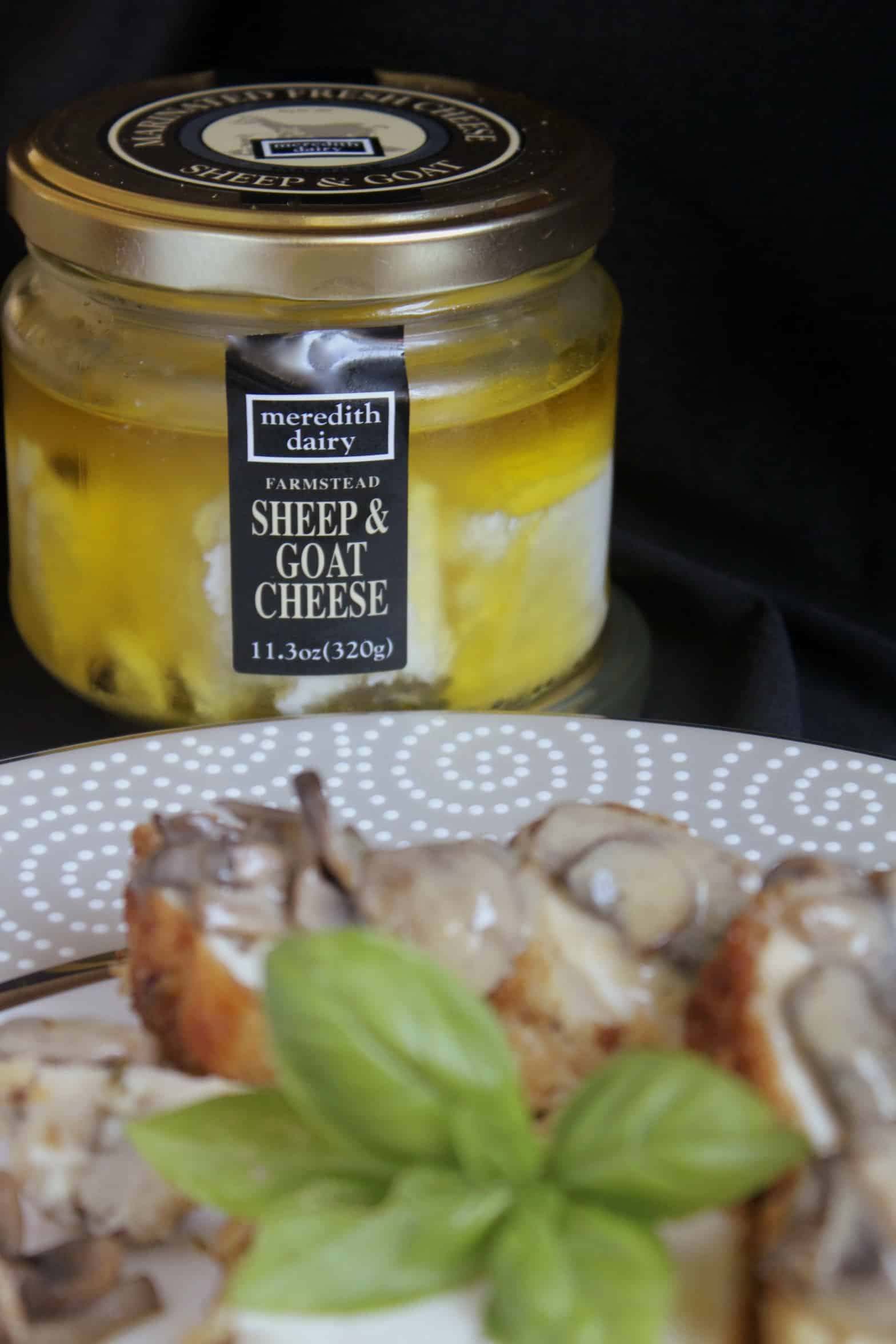 meredith dairy marinated goat cheese jar next to a plate of food
