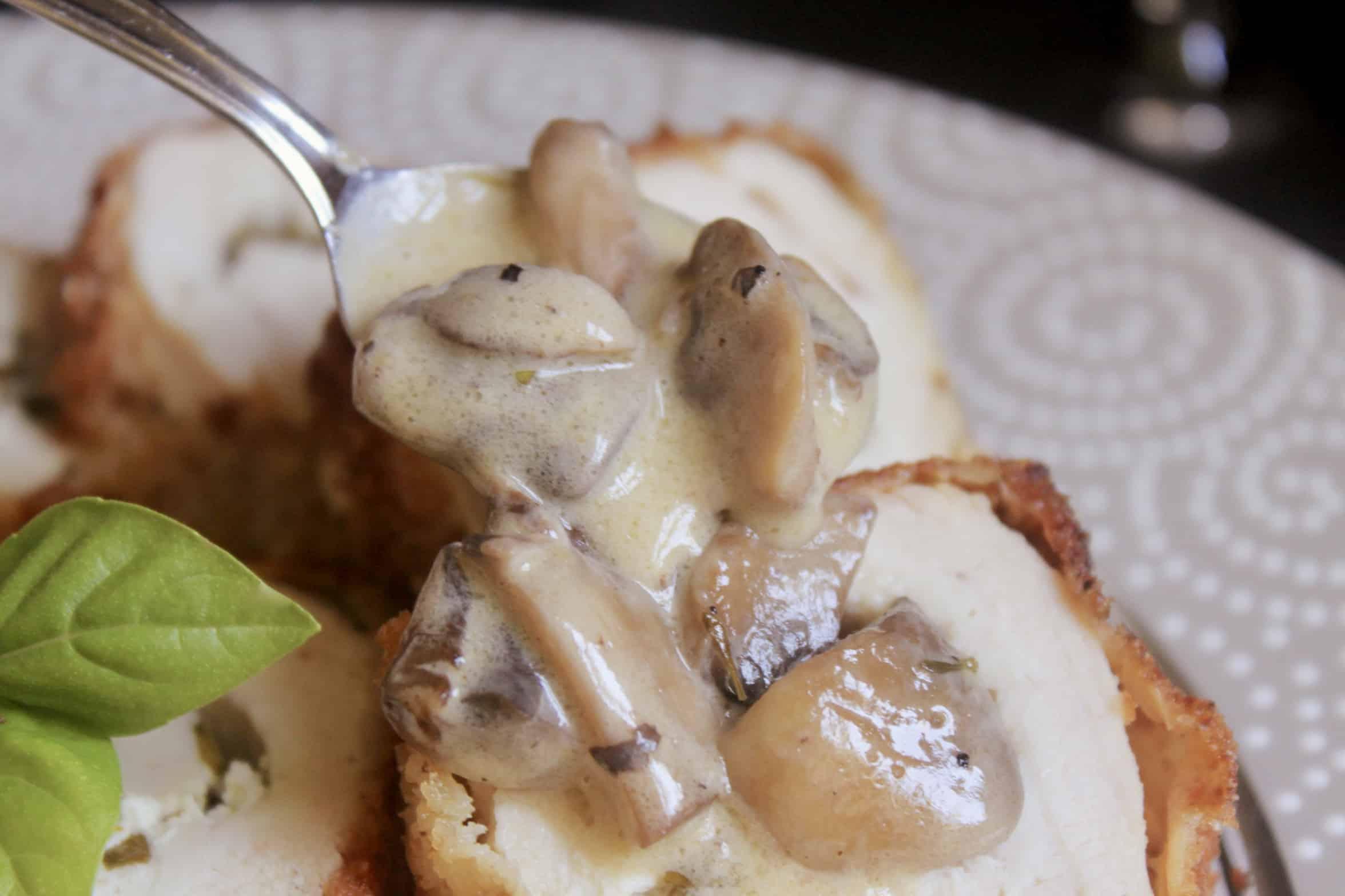 spooning mushroom sauce onto chicken