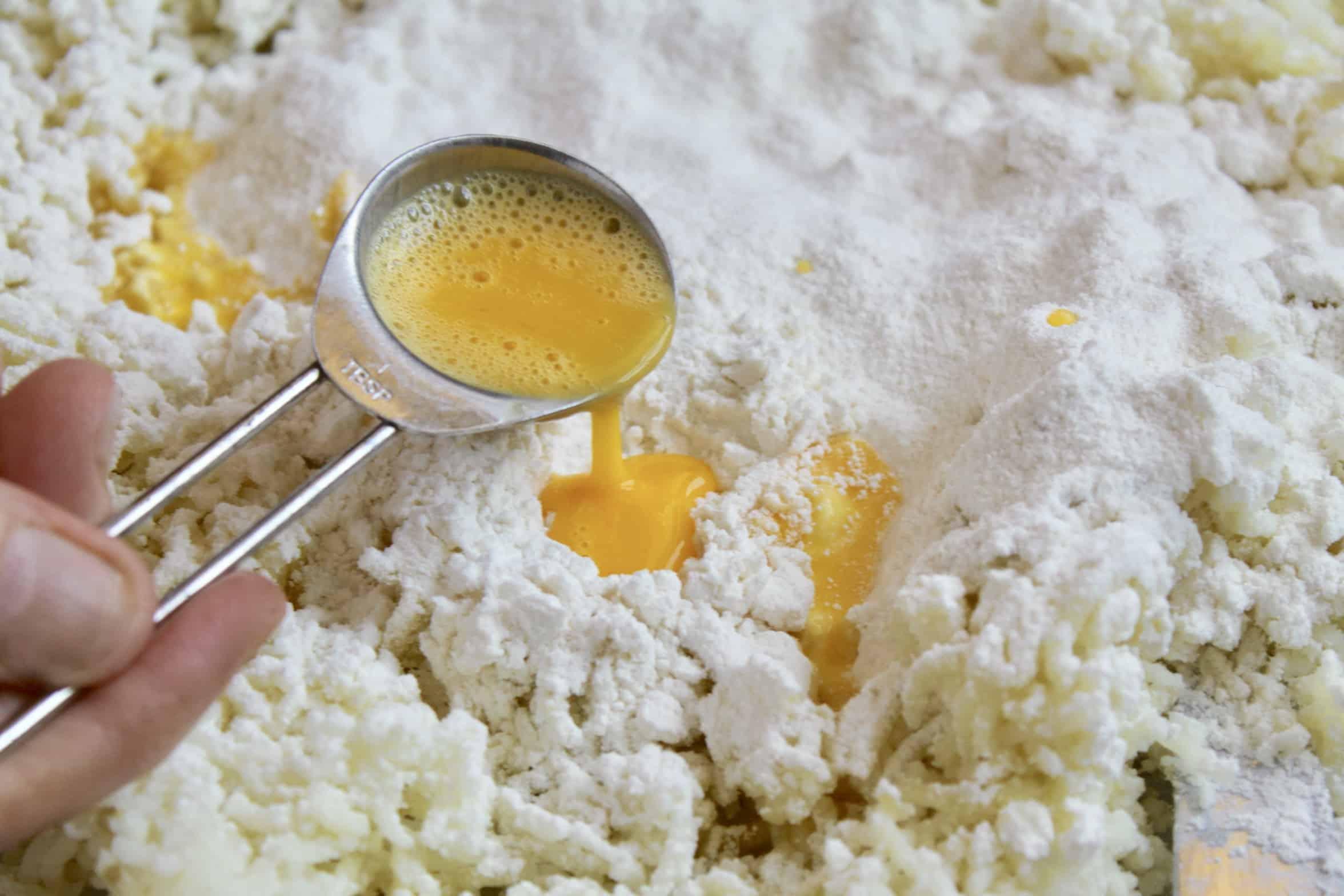 adding beaten egg to potatoes and flour
