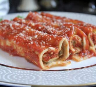 three manicotti on a fine china plate