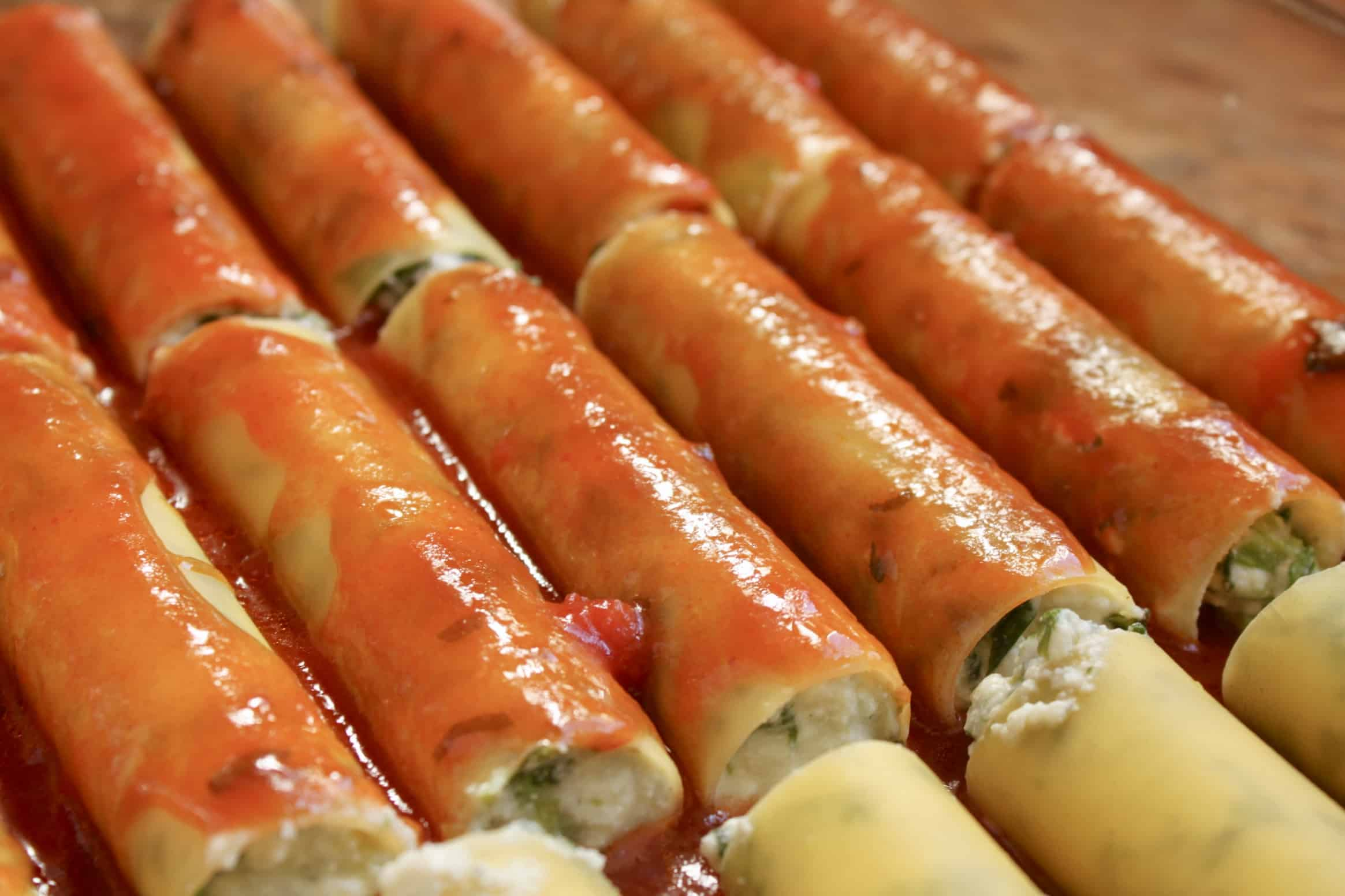 raw stuffed manicotti in a tray covered with sauce