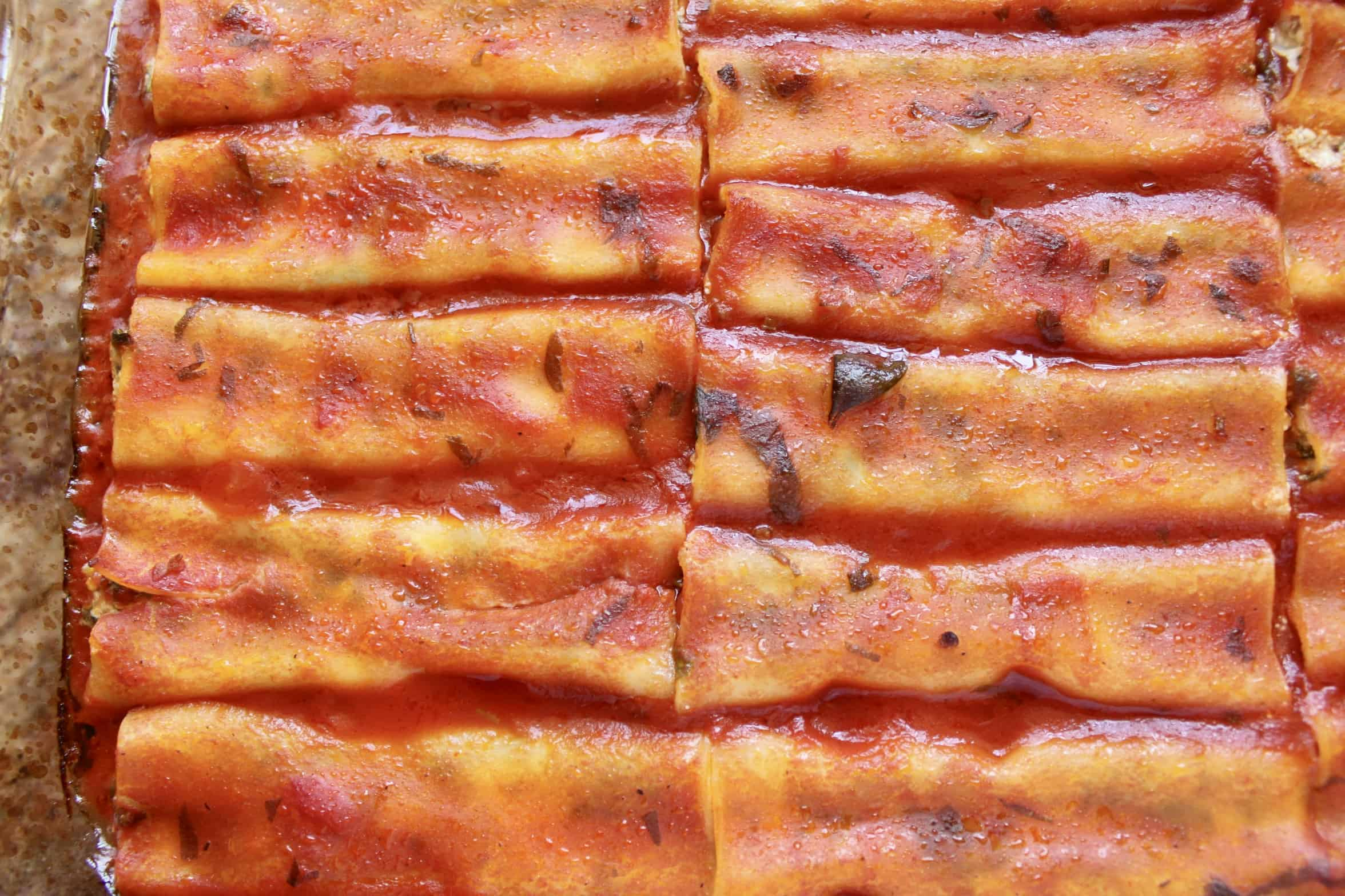 baked stuffed manicotti in a tray covered with sauce