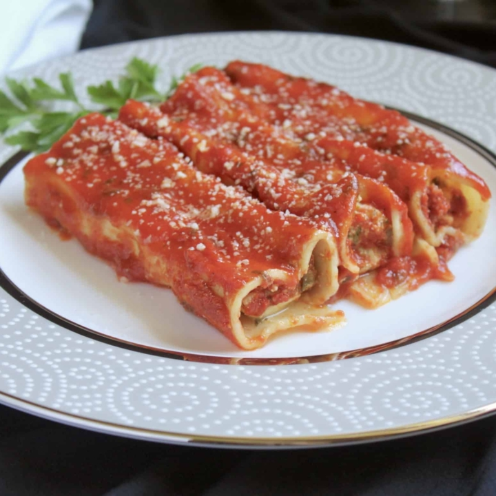 3 manicotti on a plate with parsley