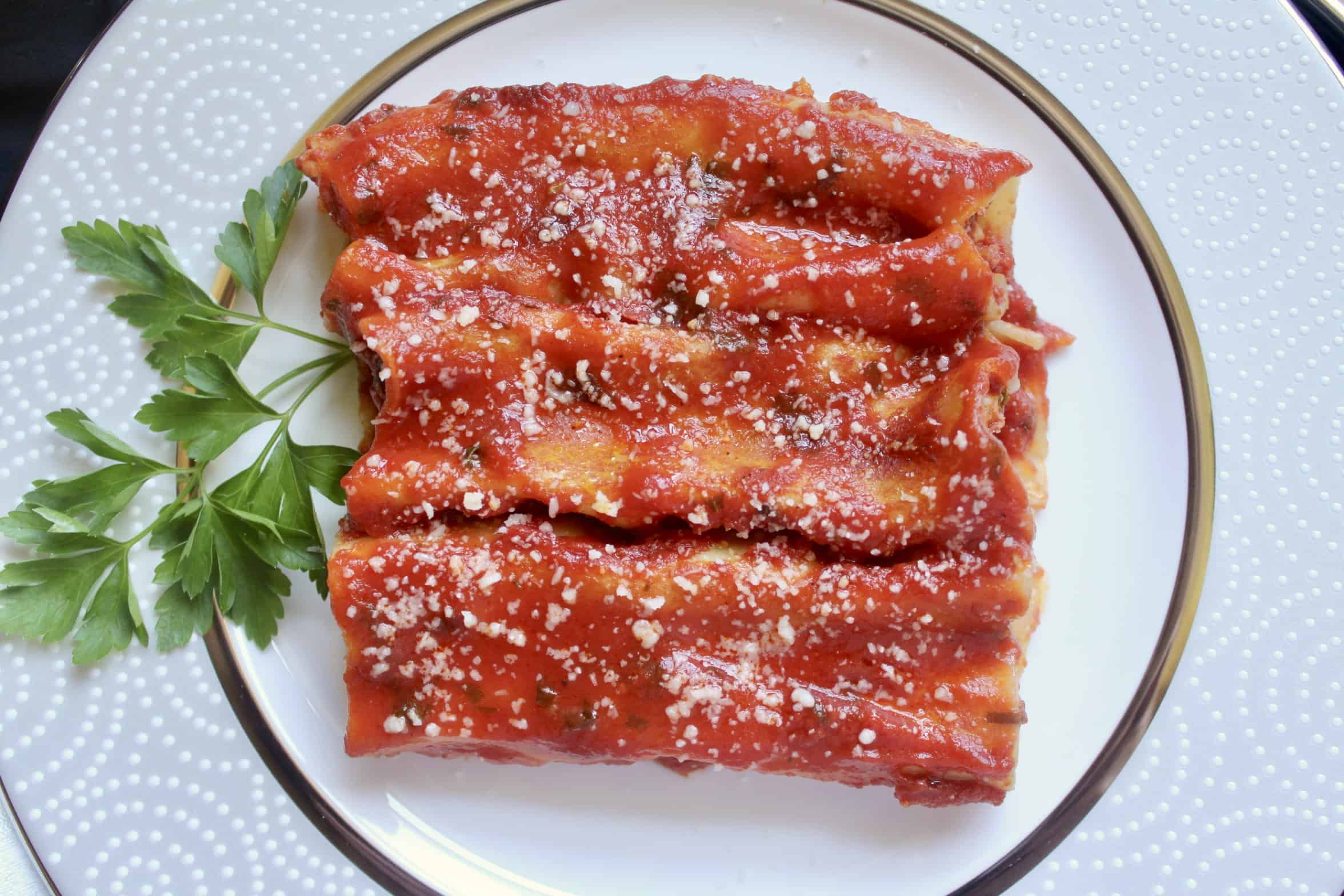 overhead shot of 3 manicotti on a pretty plate with parsley