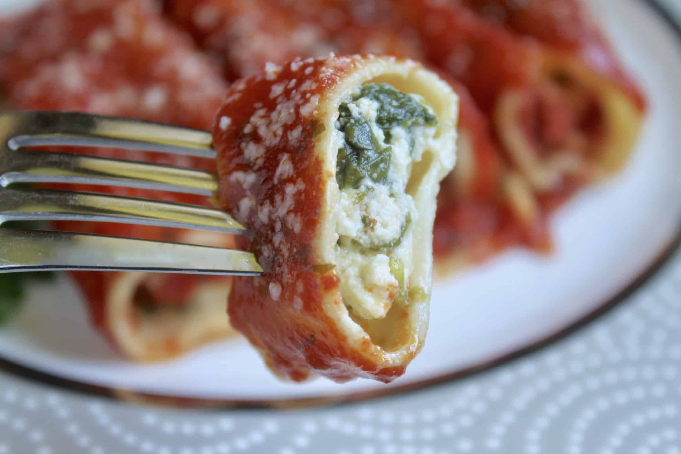 close up of a bite of manicotti on a fork