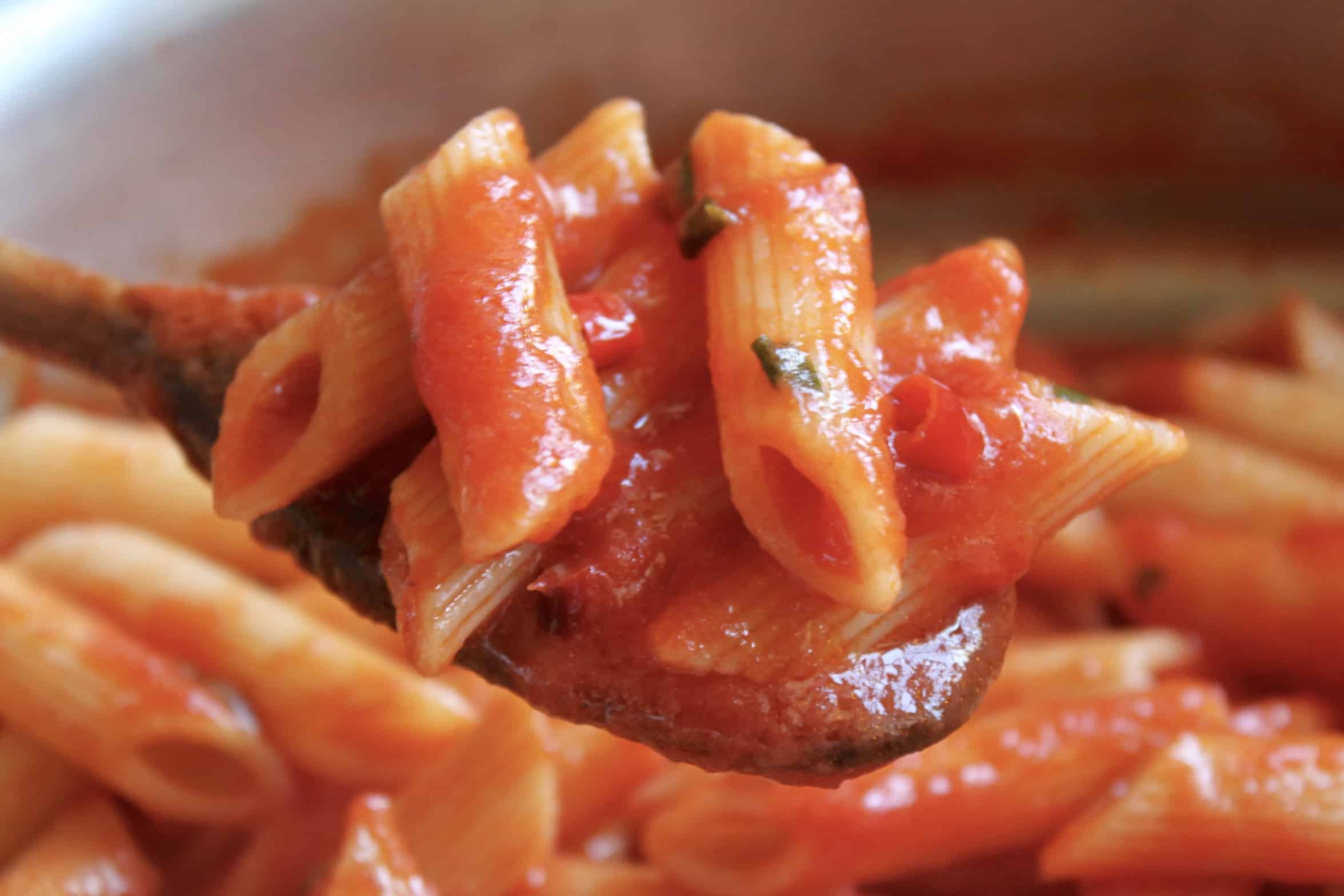 mixing sauce with penne pasta