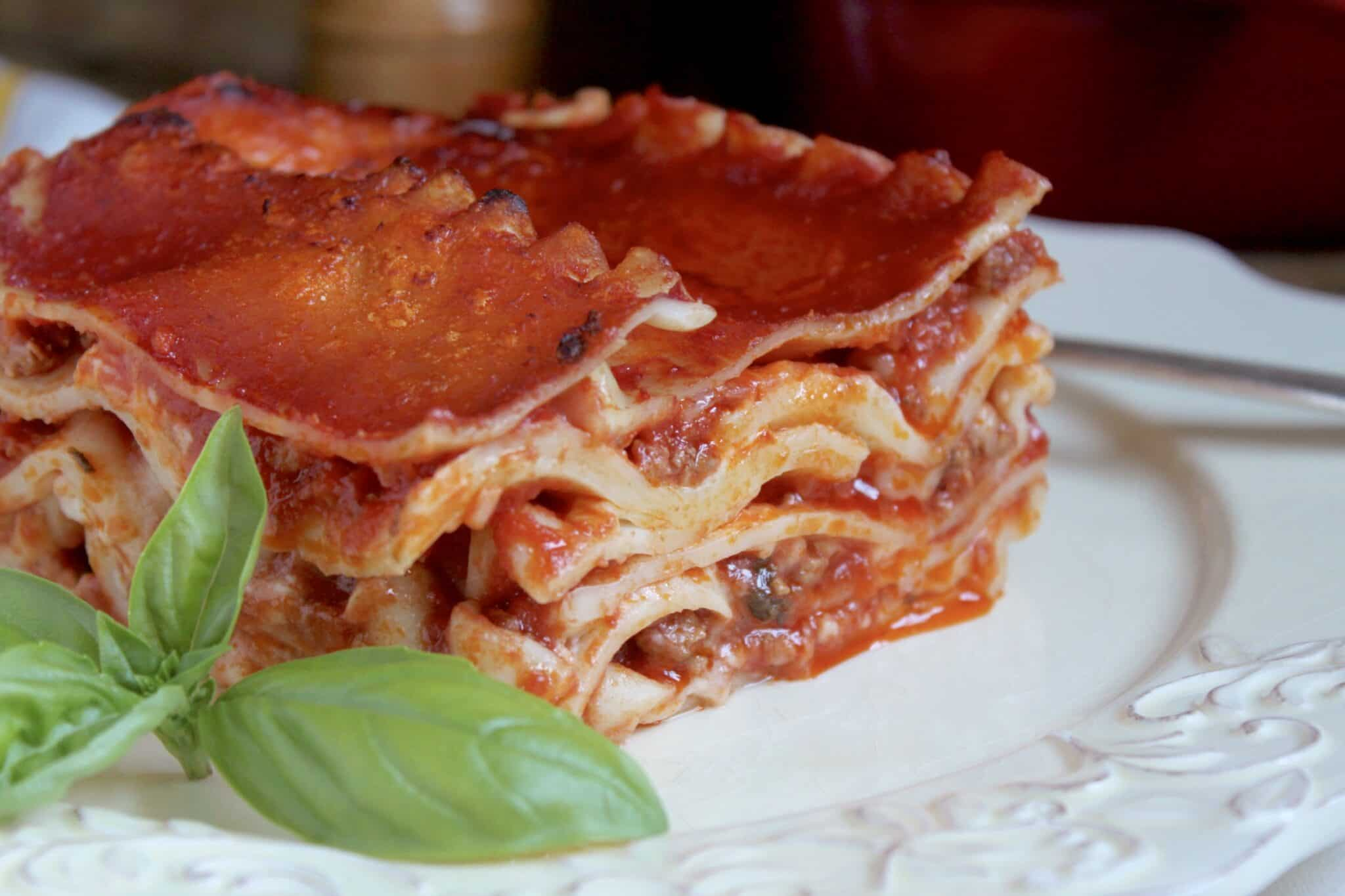 lasagna on a plate with a basil leaf