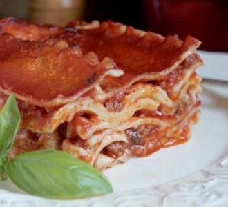 lasagna on a plate with a basil leaf