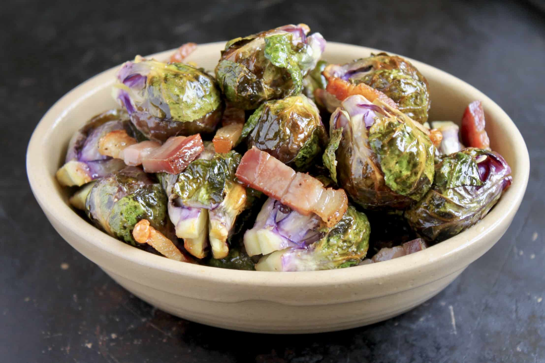 roasted brussels sprouts with pancetta in an oval dish