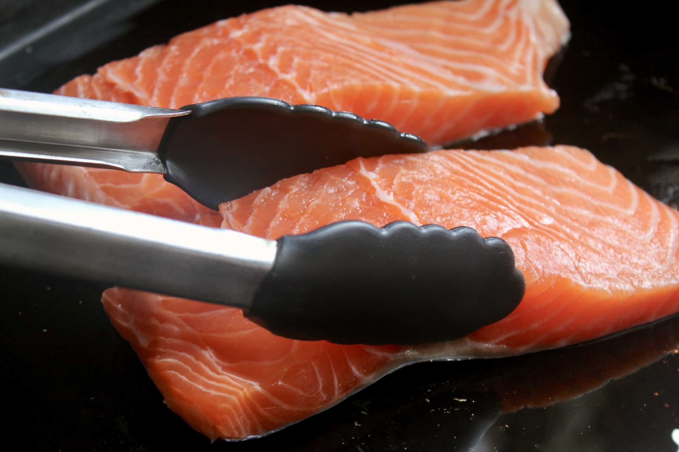 tongs placing salmon on a tray