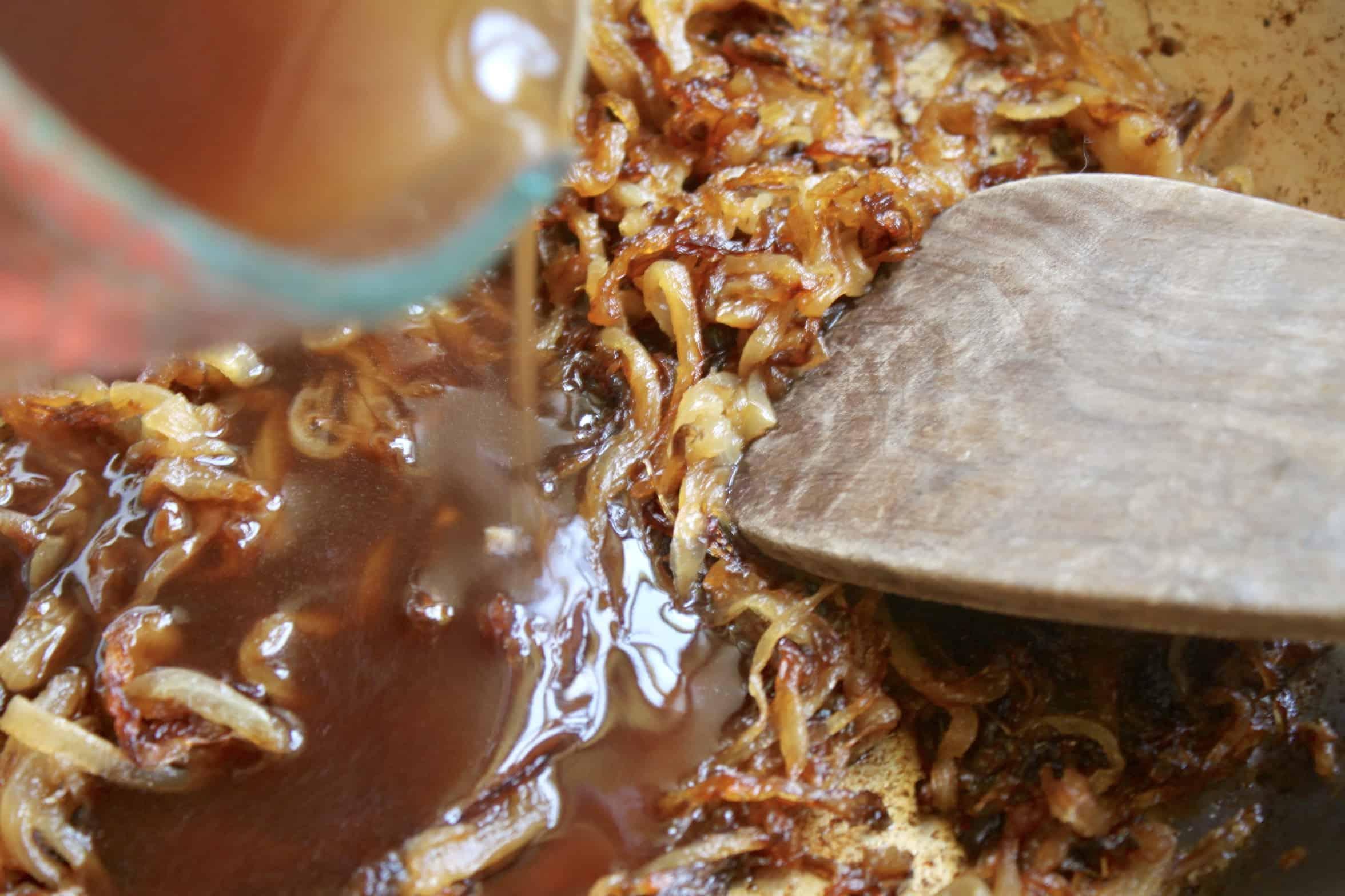 adding gravy to caramelized onions
