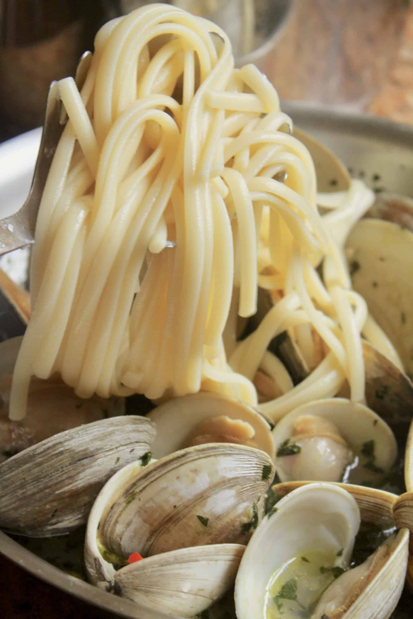 adding linguine to clams