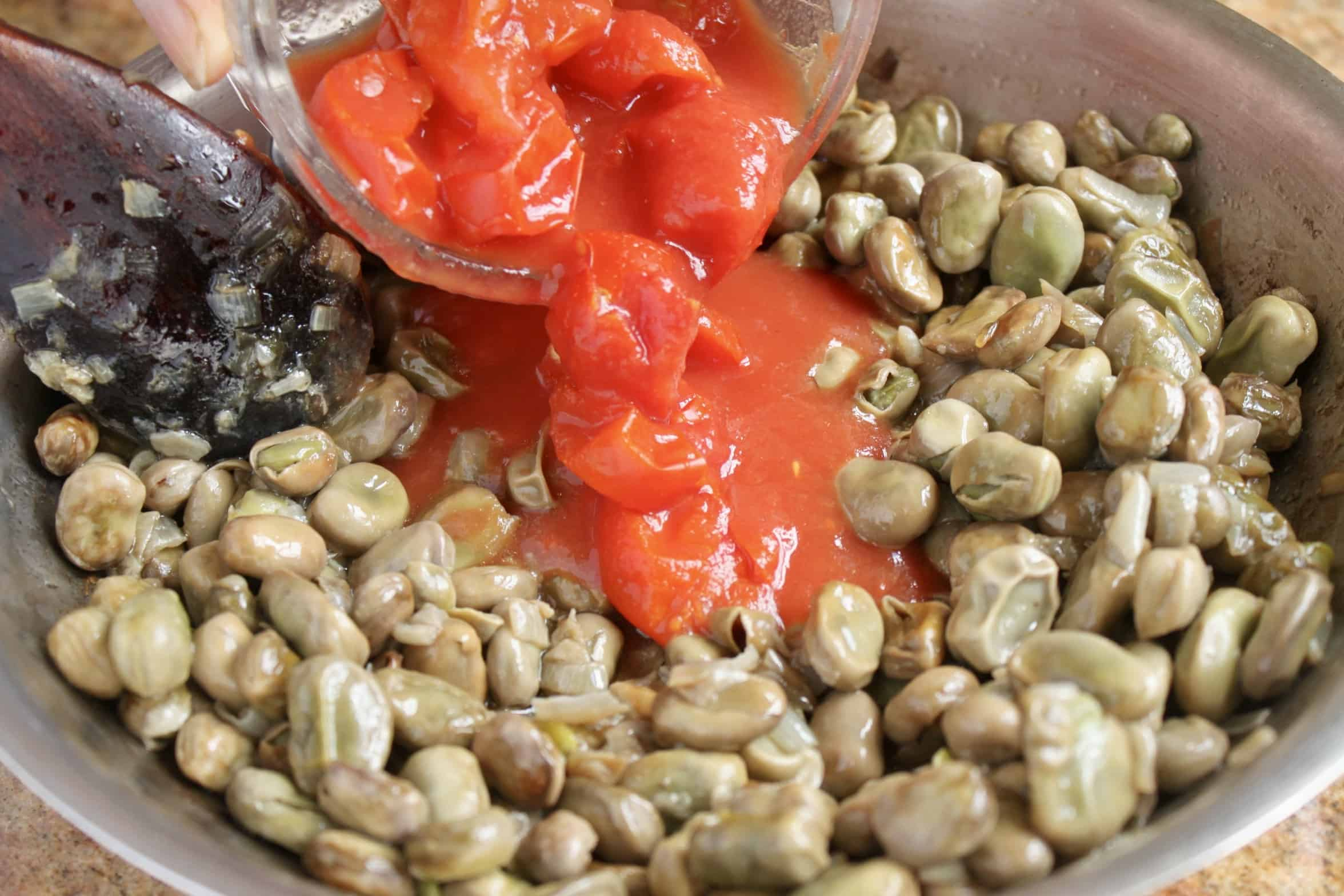 adding tomatoes to fava