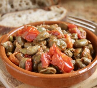 fava beans and tomatoes in a bowl with bread
