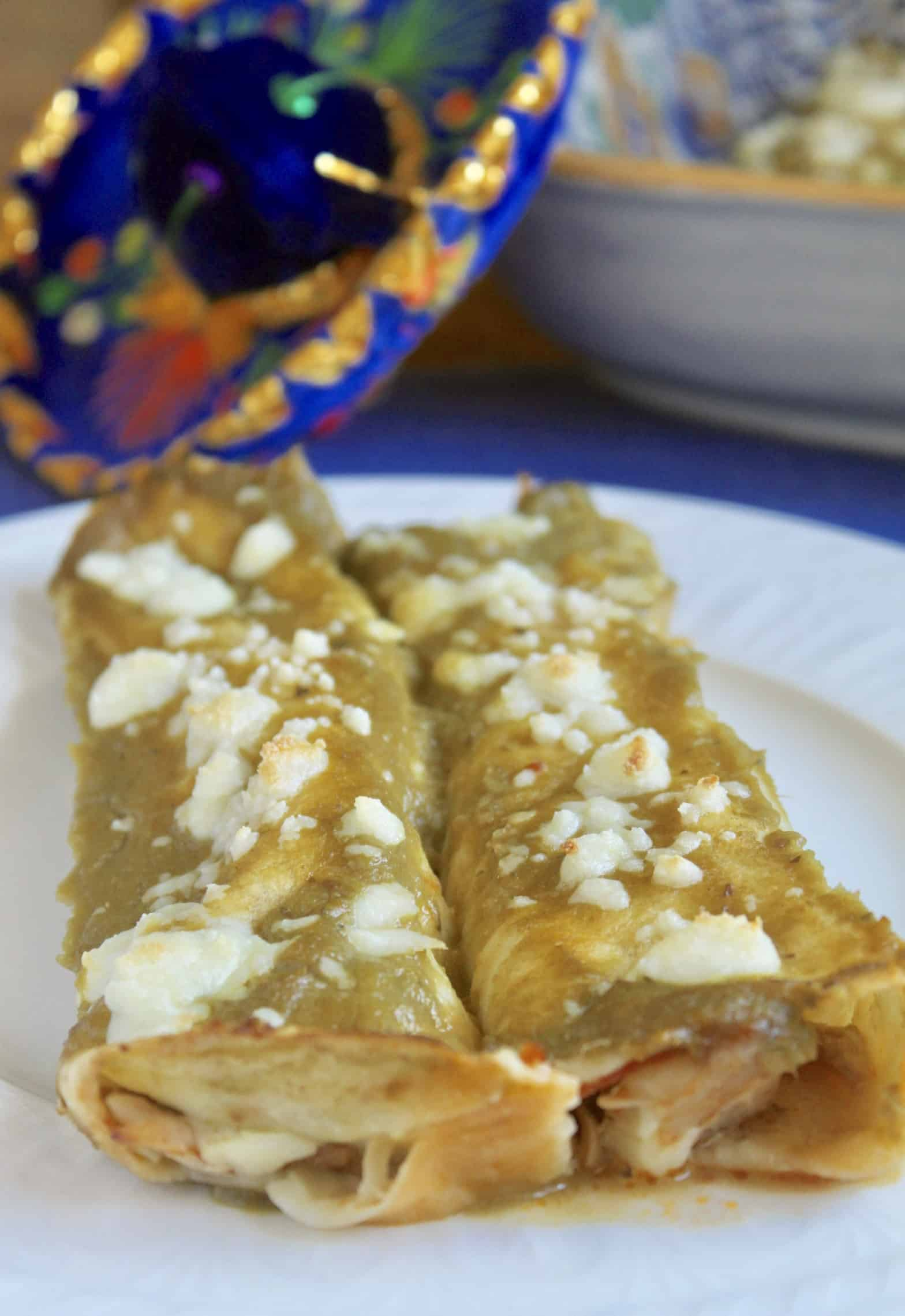 Green chicken enchiladas on a plate with a Mexican hat