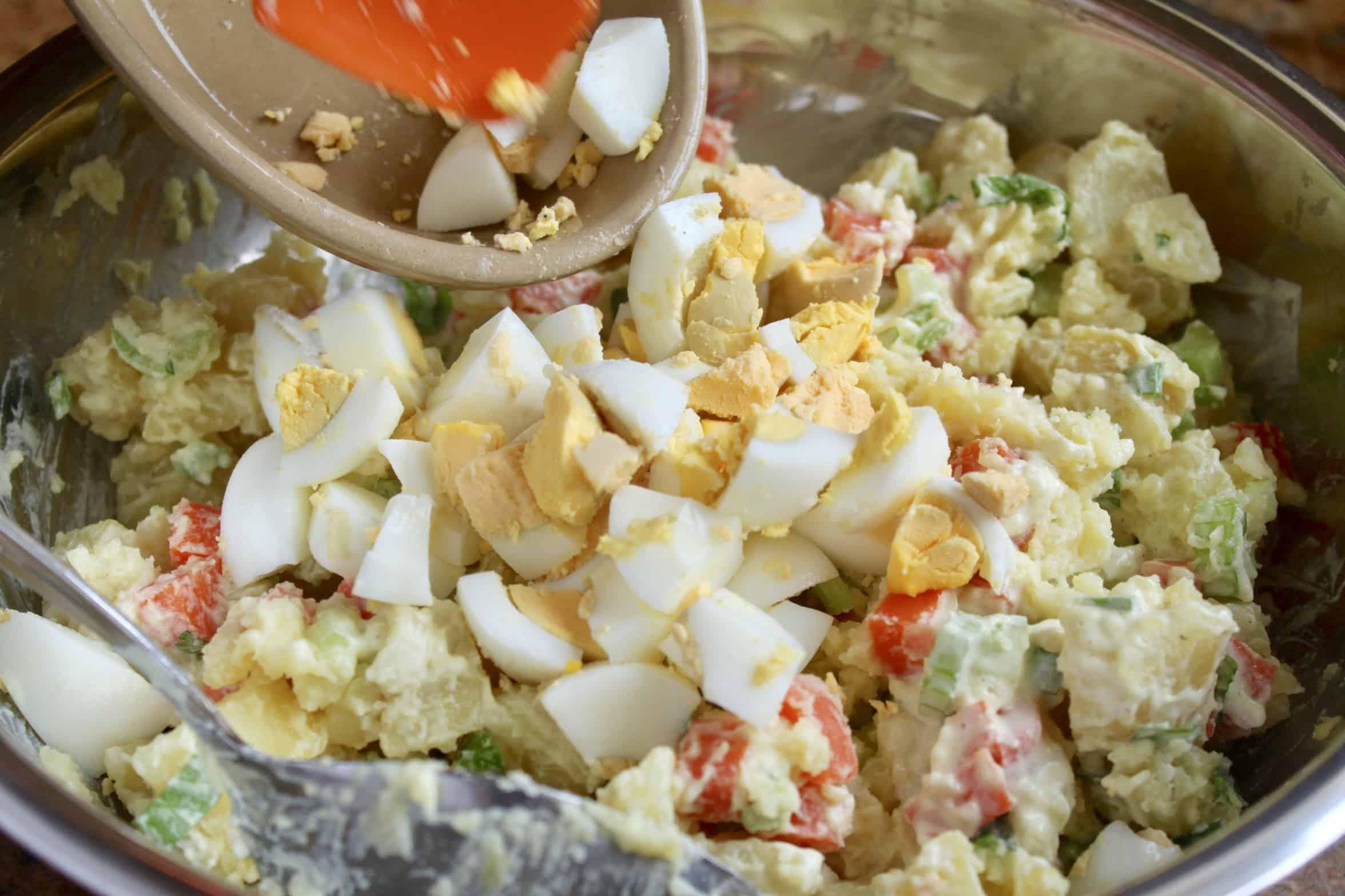 adding eggs to Korean potato salad