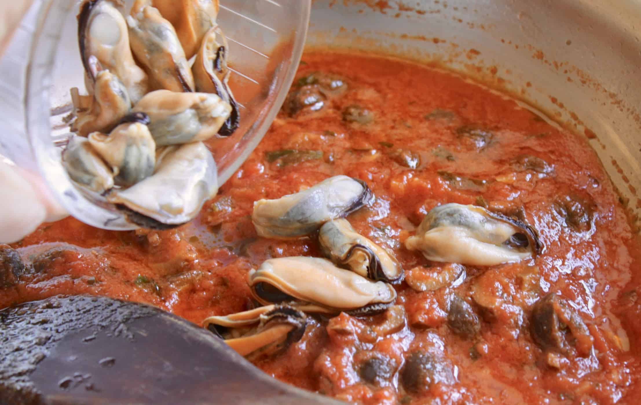 adding mussels to the sauce