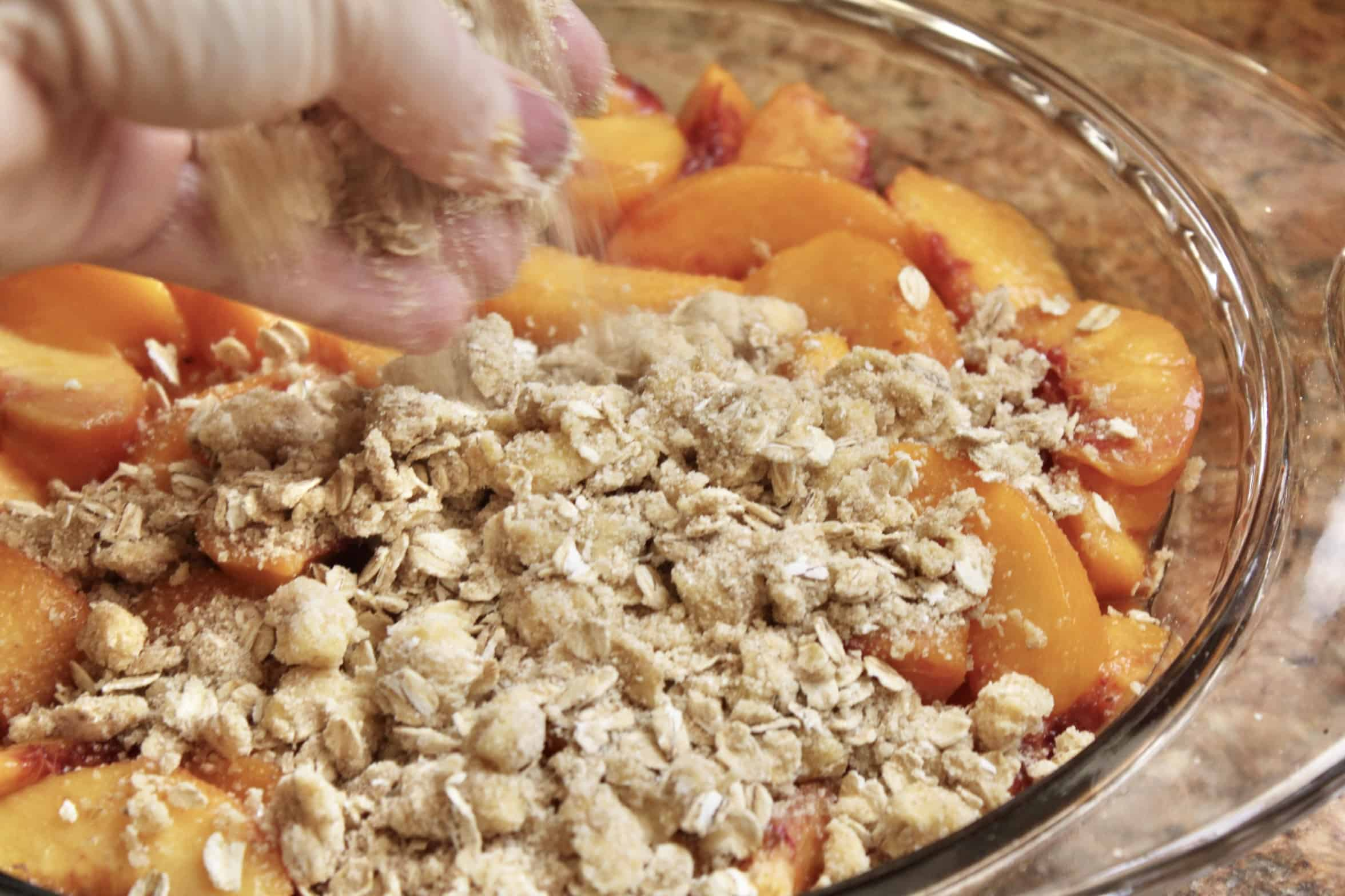 sprinkling crisp topping onto peaches