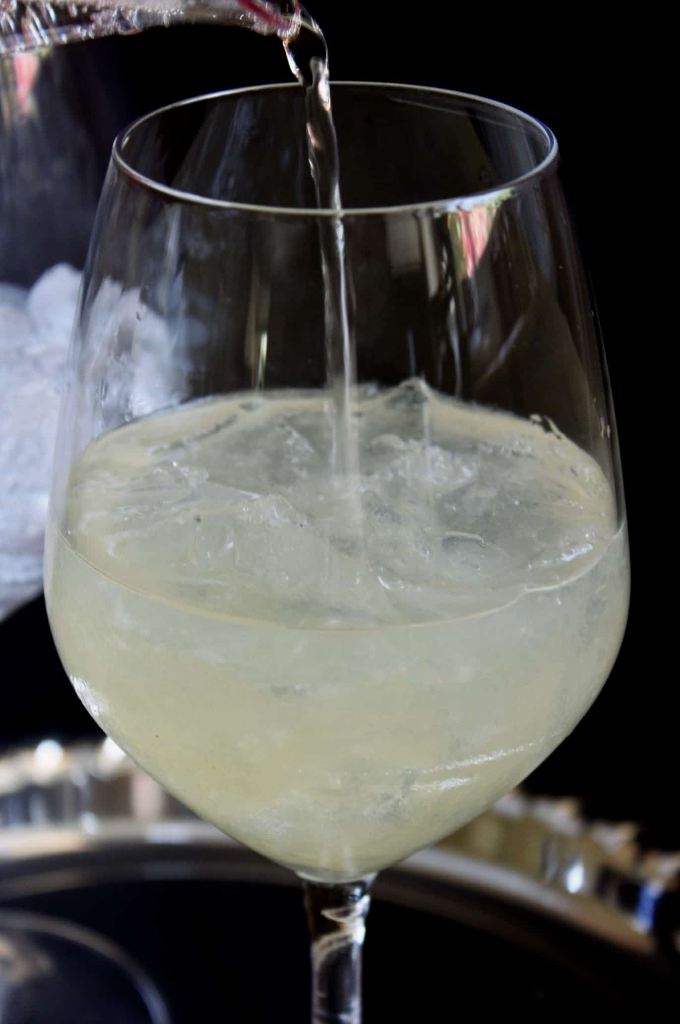 adding prosecco to the cocktail