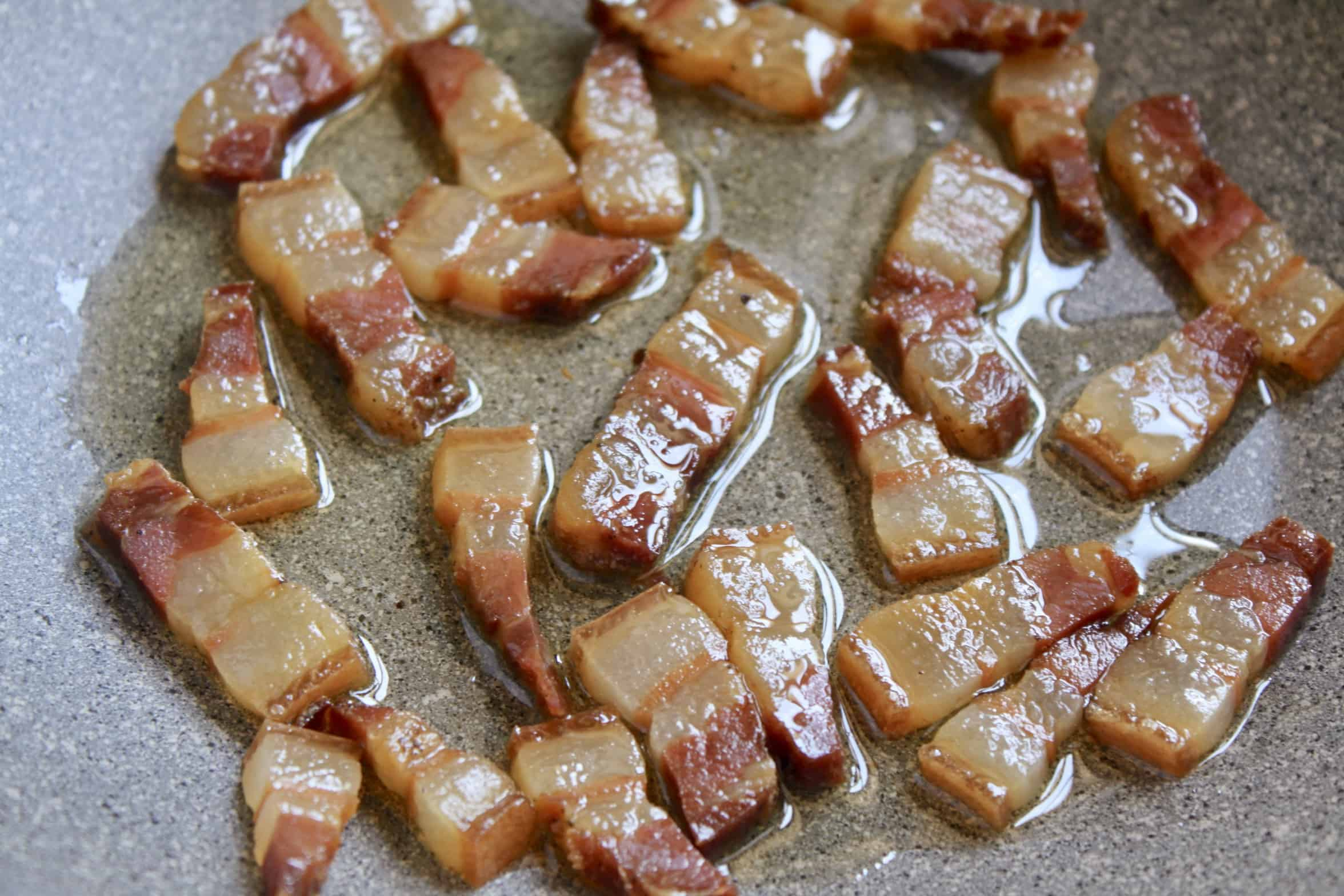 pieces of pancetta frying in a pan