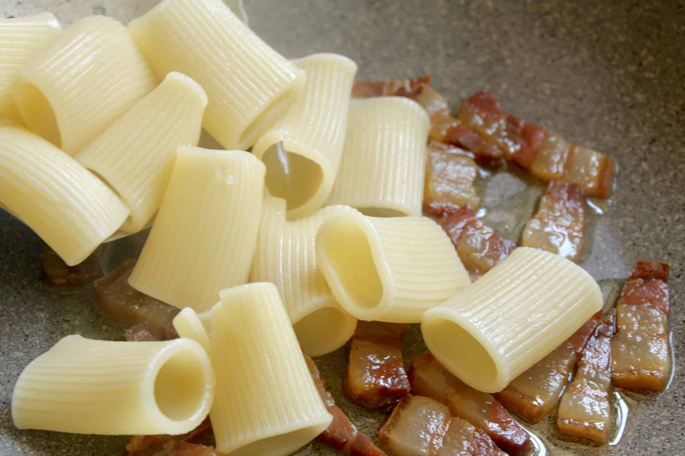adding rigatoni to the other pan