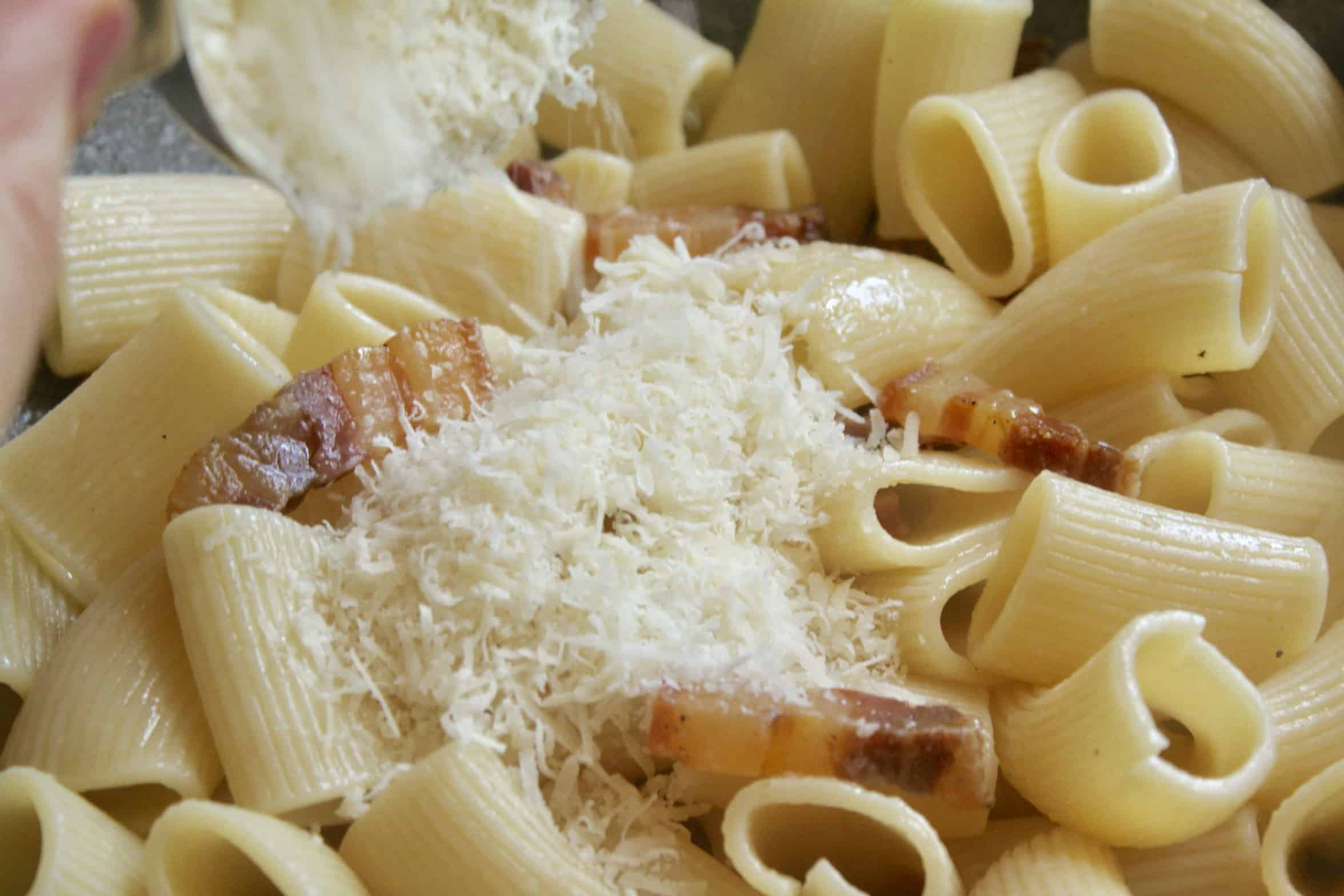 adding Parmigiano to the pancetta pasta