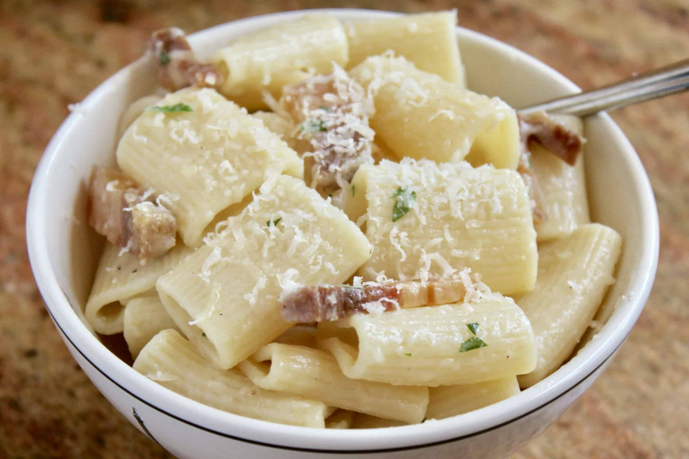 pancetta pasta in a bowl with cheese on top