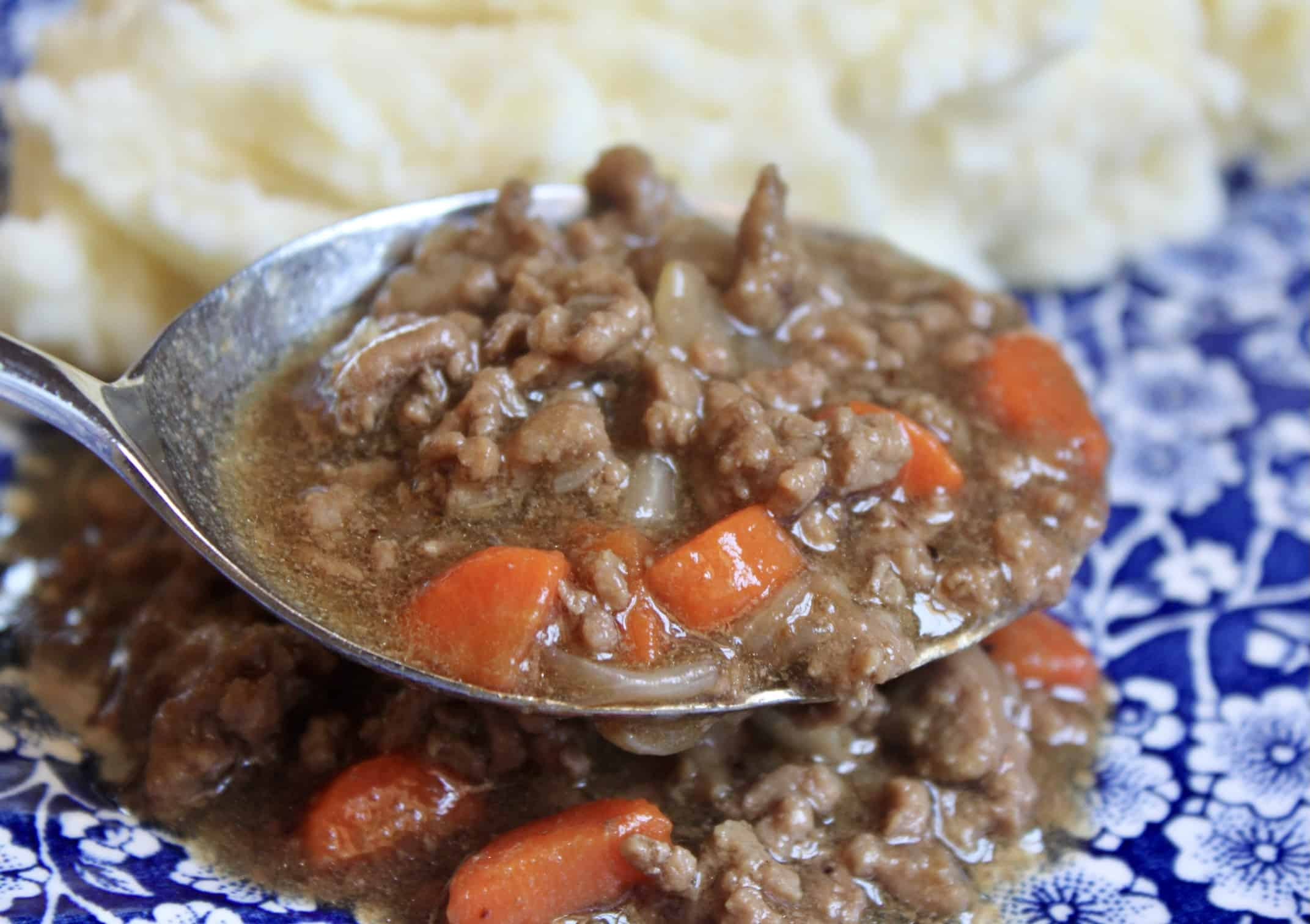 spooning out mince onto a plate with potatoes